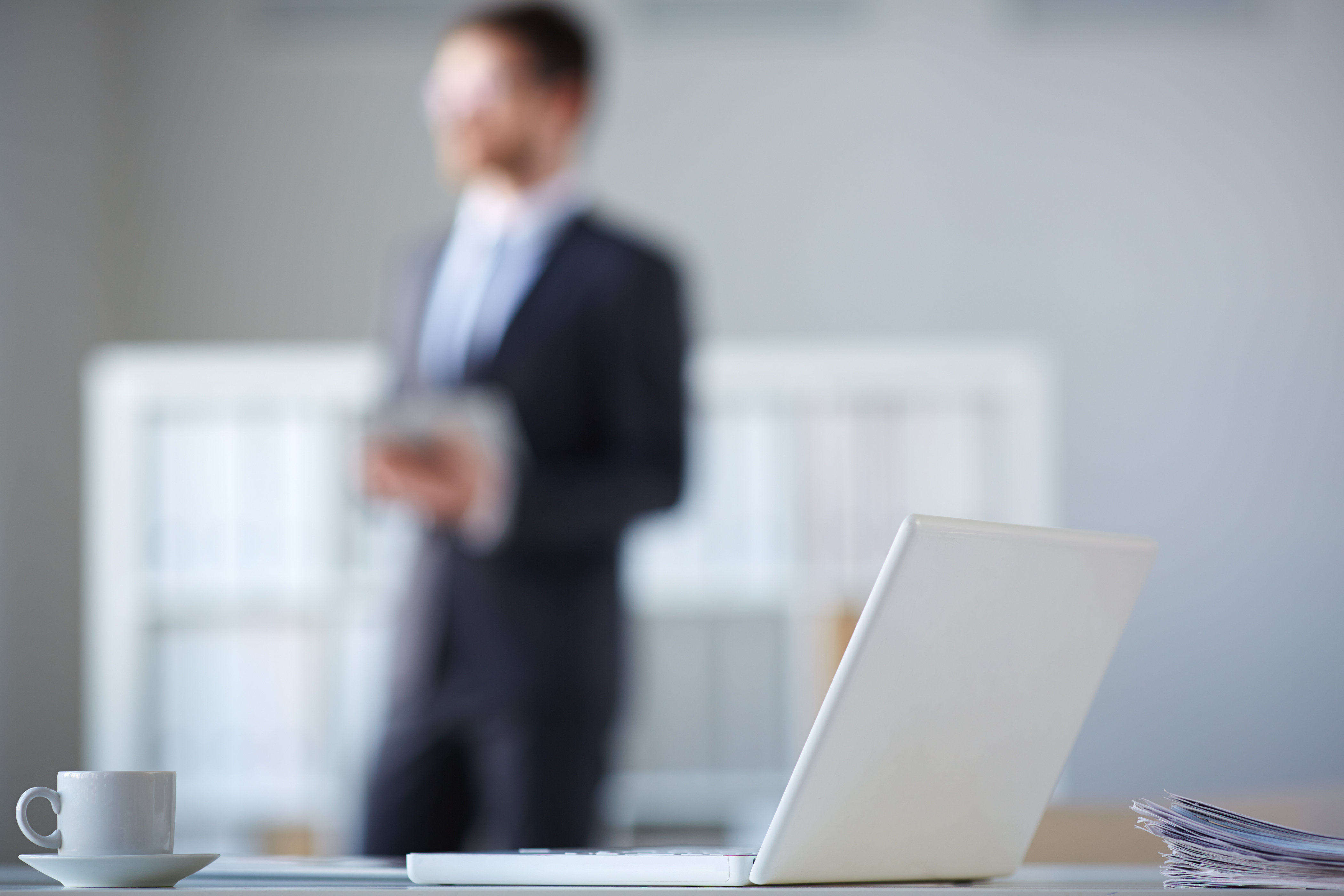 Open laptop, pile of papers and cup at workplace with businessman on background
